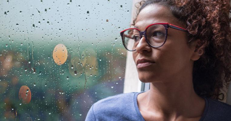 woman against rainy window